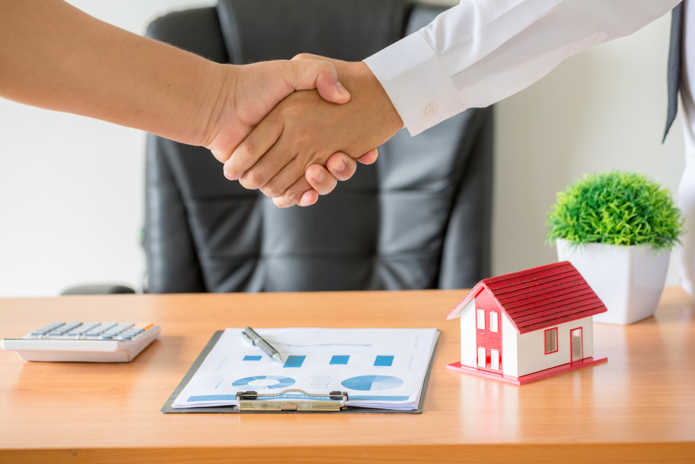 Two persons shaking hands over property deed transfer.