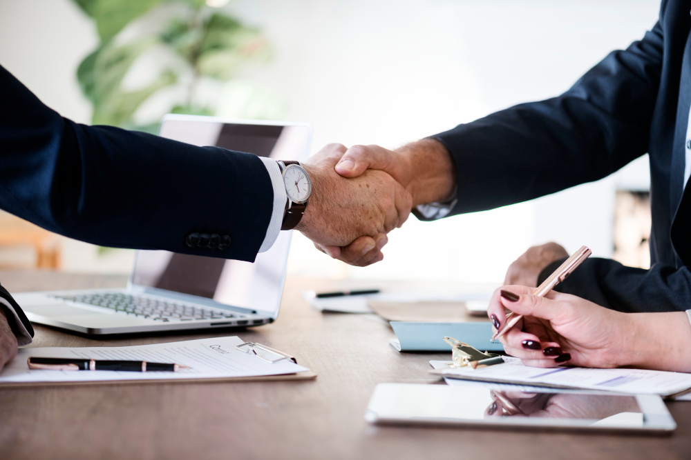 Two business people shaking hands. Real estate investment llc formation & setup.